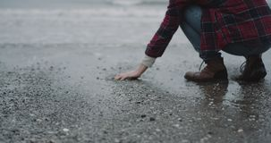 Closeup capturing video of a man beside of a seashore on rain day , he took some wet sand on his hand and throw down. Meditation time stock footage