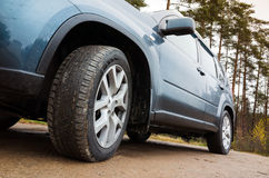 Closeup car fragment, wheel on dirty road Royalty Free Stock Image