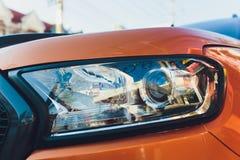 Closeup of car headlight - front view orange body. royalty free stock image