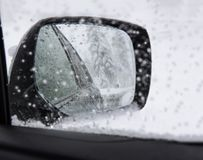 Driving in snowfall. Car side mirror with snowflakes. Royalty Free Stock Photos