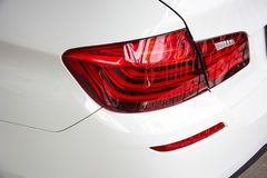 Closeup of car tail light on white car. Royalty Free Stock Photo