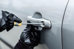 Closeup on car thief hands trying to steal a vehicle. Close up on car thief hands trying to steal a vehicle with screwdriver Royalty Free Stock Image