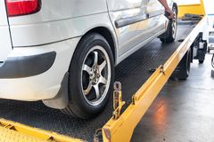 Closeup on car towed onto flatbed tow truck with cable. Closeup of broken down car being towed onto flatbed tow truck with cable for repair at workshop garage royalty free stock image