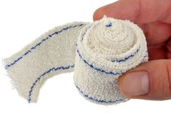 Coiled bandage held in hand on a white background royalty free stock image