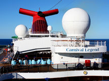 Closeup of Carnival Legend cruise ship. Closeup image of deck of Carnival Legend with passengers relaxing in deck chairs, bright red funnel and white radar domes stock photo