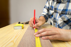 Closeup of carpenter measuring the wooden plank Royalty Free Stock Image