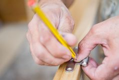 Closeup of carpenter with pencil working on door Stock Images