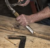 Closeup of carpenter`s rough hands chiseling wood board using hammer royalty free stock photo