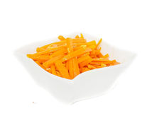 Closeup of carrot cut into julienne slices. In a beautiful white bowl against white Stock Photos