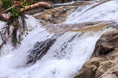 Closeup Cascade of Foamy Waterfalls along Brown Stones Stock Images