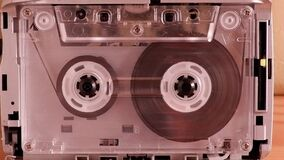 Closeup cassette tape with clear body playing music audio or recording, retro, vintage, Analogue gadgets for the 70-80-90s