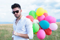 Closeup of casual man with balloons and sunglasses Royalty Free Stock Photo