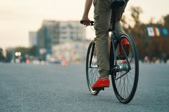 Closeup of casual man legs riding classic bike on city road royalty free stock image