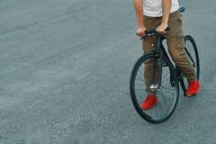 Closeup of casual man legs riding classic bike on city road royalty free stock photos