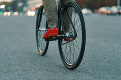 Closeup of casual man legs riding classic bike on city road royalty free stock photography