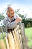 Closeup of casual senior man leaning on wood fence Stock Photo