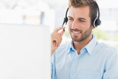 Closeup of a casual young man with headset using computer Royalty Free Stock Photography