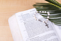 Closeup Catholic rosary with crucifix and beads on Holy Bible Stock Images