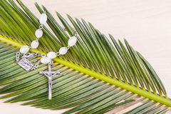 Closeup Catholic rosary with crucifix and beads on palm leaf Stock Photos
