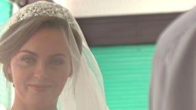 Closeup Caucasian Bride in White Lacy Dress Sets Veil Straight. Closeup beautiful caucasian bride in elegant white lacy dress sets veil straight in muslim mosque stock footage