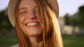 Closeup caucasian cheerful girl in hat with amazing red long hair laughing looking at camera during bright sunny day on