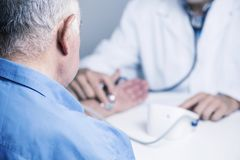 Doctor measuring the blood pressure of a senior royalty free stock image