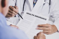 Doctor showing a health insurance policy to a man royalty free stock photography