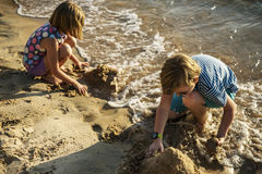 Closeup of caucasian kids playing with the sand together at the. Beach Royalty Free Stock Image