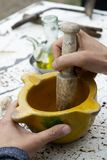 Man using a mortar and pestle. Closeup of a caucasian man preparing a homemade sauce or grinding some ingredients in an old ceramic mortar, with a wooden pestle royalty free stock image