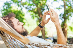 Closeup of a caucasian man using mobile phone white swinging in Stock Photo