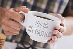 Coffee and text happy fathers day in spanish. Closeup of a caucasian man with a white ceramic cup with coffee in his hands, with the text feliz dia del padre royalty free stock photo