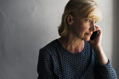 Closeup of caucasian woman calling mobile phone with thoughtful face expression Stock Photo