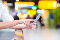 Closeup cell phone at airport in female hands Royalty Free Stock Image