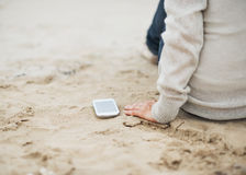 Closeup on cell phone near woman sitting on beach Royalty Free Stock Images