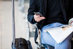 Closeup cellphone in male hands at the airport while waiting for boarding. Stock Photography