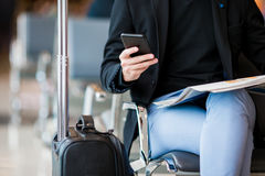 Closeup cellphone in male hands at the airport while waiting for boarding. Stock Photo
