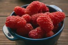 Closeup of ceramic bowl with raspberries. Low angle shot Stock Photos