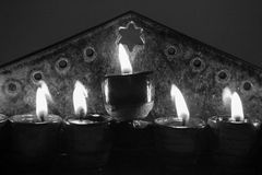 Closeup Ceramic hanukiah lit with 4 candles and shamash in b. Hanoukkah candlestick with olive oil Stock Image
