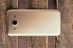 Closeup of champagne color smart phone, on wooden table, top vie. Top view of a single smart phone of champagne color, on vintage grunge wooden table. Closeup royalty free stock photography