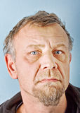 Closeup character portrait of a man. With blue eyes, dressed in an old hooded jacket looking at the camera with questioning and suspicious facial expression Royalty Free Stock Image
