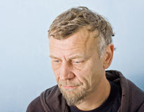 Closeup character portrait of a man. With blue eyes, dressed in an old hooded jacket with face expressing depression and disappointment Royalty Free Stock Photo