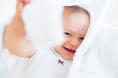 Closeup of a cheerful cute baby under comforter Royalty Free Stock Photography