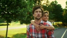 Father giving son piggyback riding in park. Man and boy talking on street