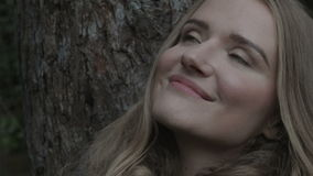 Closeup of cheerful woman sitting on a bench in a park during autumn time. stock video footage