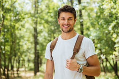 Closeup of cheerful young man standing and smiling in forest Stock Photography