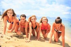 Closeup cheerleaders in bikinis crawl in line along wet sand Royalty Free Stock Photography