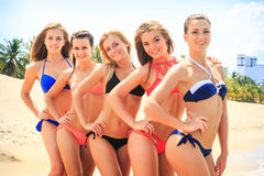 Closeup cheerleaders in bikinis stand closely in line on beach Stock Images