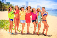 Closeup cheerleaders in t-shirts bikinis stand in line on beach Royalty Free Stock Photography