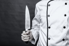 Closeup of a chef  holding a big sharp knife. Over gray background Stock Photos