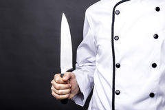 Closeup of a chef  holding a big sharp knife. Over gray background Stock Photography